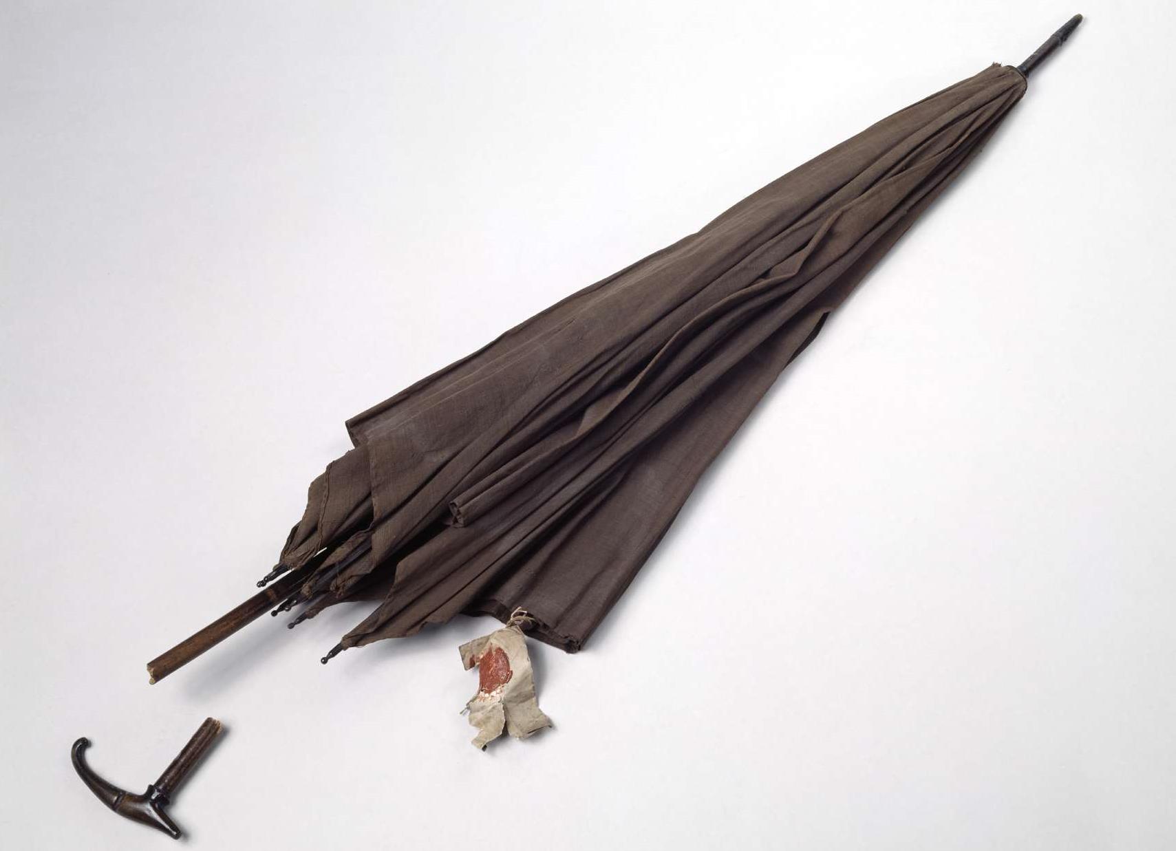 Das Foto zeigt einen alten Regenschirm mit Etikett.