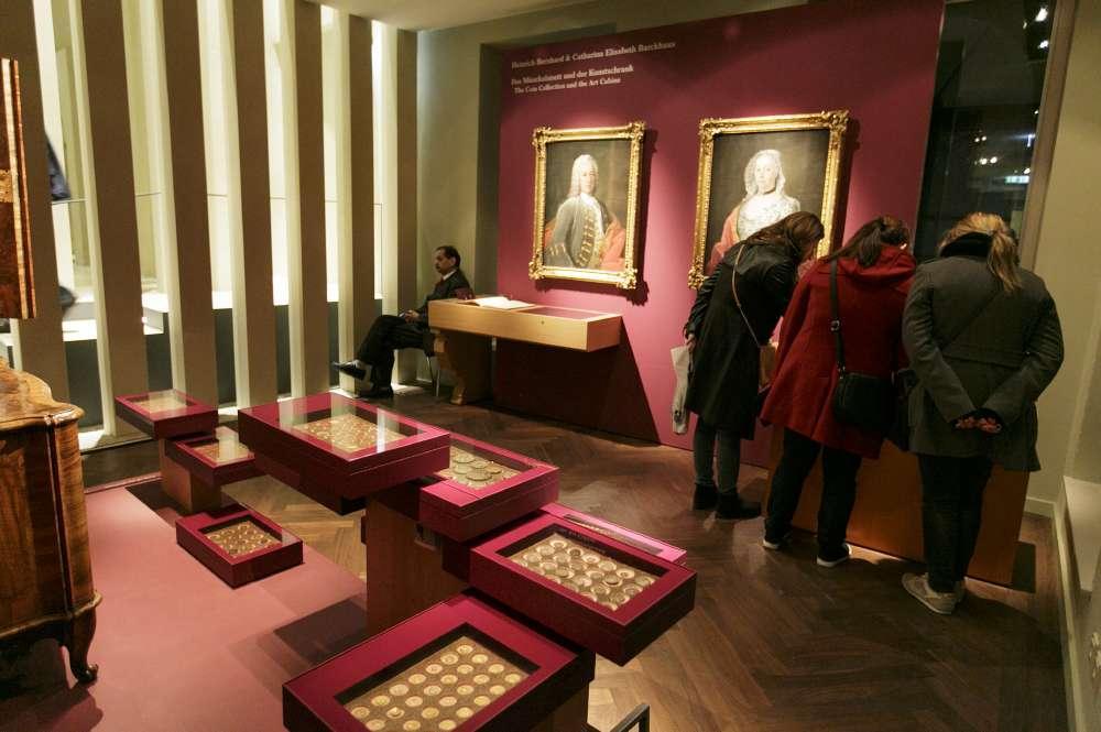 Besucher betrachten Münzen aus der Sammlung Glock/Barckhaus