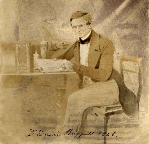 Eine Gemälde zeigt Edouard Rüppell sitzend eine Zeitungs lesend im Jahr 1846