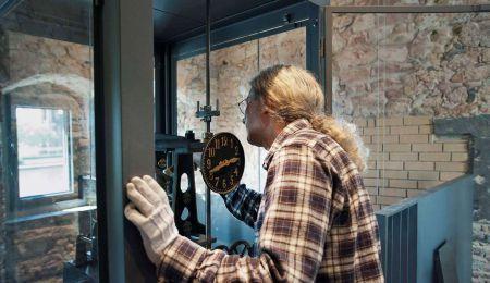 Mann arbeitet an historischer Pendeluhr im Rententurm