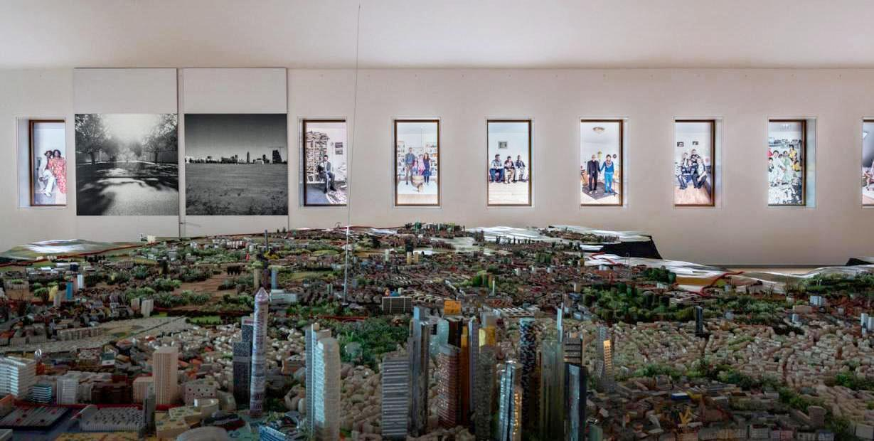 Ein Foto zeigt eine Ausstellungsansicht aus der Dauerausstellung in Frankfurt Jetzt! Im Vordergrund ist das Frankfurt-Modell zu sehen, im Hintergrund sind in den Fenstern einige Porträts von Anna Pekala und auf der Wand zwei Stadtansichten von Florian Albrecht-Schoeck.