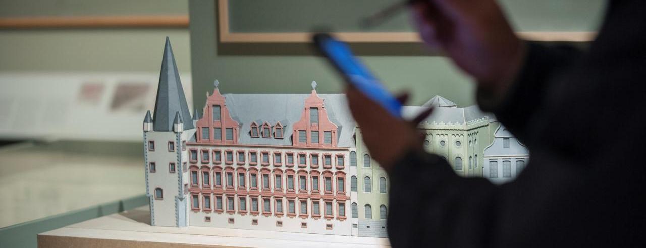 Das Foto veranschaulicht die digitale Museumspraxis im HMF: eine Smartphonenutzerin beim Tweet up in der Sonderausstellung Burnitz